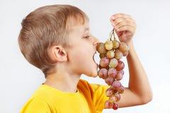 Rapaz pequeno em uma camisa amarela que come a uva Imagens de Stock