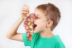Rapaz pequeno em uma camisa verde que come a uva madura Imagens de Stock