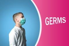 Rapaz pequeno em uma máscara médica em um fundo brilhante com GERMES da inscrição imagens de stock