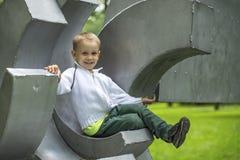 Rapaz pequeno engraçado bonito que senta-se no campo de jogos em um parque da cidade feliz Foto de Stock