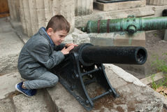 Rapaz pequeno engraçado com uma arma pequena velha Imagens de Stock