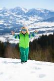 Rapaz pequeno engraçado nos óculos de sol em montanhas do inverno em um d ensolarado Fotografia de Stock