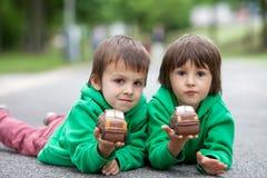 Rapaz pequeno engraçado que joga com o carro do chocolate, exterior Imagem de Stock