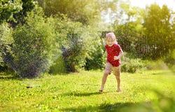 Rapaz pequeno engra?ado que joga com o sistema de extin??o de inc?ndios do jardim no quintal ensolarado fotografia de stock