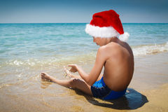 Rapaz pequeno engraçado com o chapéu de Santa que senta-se na praia Fotos de Stock