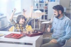 Rapaz pequeno entusiasmado que comemora sua vitória da xadrez fotografia de stock