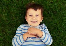 Rapaz pequeno entusiasmado que encontra-se na grama verde Imagem de Stock