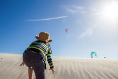 Rapaz pequeno entusiasmado que escala a duna de areia ventosa para olhar o surfista do papagaio Fotografia de Stock Royalty Free