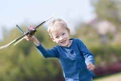Criança que joga com um plano fotografia de stock royalty free