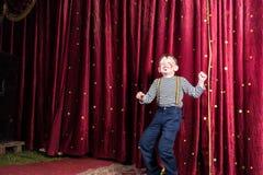 Rapaz pequeno exuberante que executa na fase fotos de stock