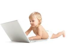Rapaz pequeno eyed azul que trabalha no portátil imagens de stock