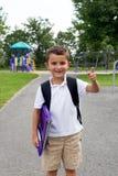 Rapaz pequeno feliz com trouxa e livro da escola na jarda do jogo fotos de stock royalty free