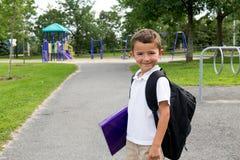 Rapaz pequeno feliz com trouxa e livro da escola na jarda do jogo imagem de stock