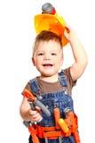 Rapaz pequeno feliz em um capacete alaranjado e ferramentas em um backgr branco Fotografia de Stock Royalty Free