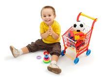 Rapaz pequeno feliz, jogando com brinquedos novos Fotografia de Stock Royalty Free