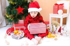 Rapaz pequeno feliz no chapéu de Santa com presente Fotografia de Stock