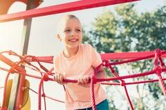 Rapaz pequeno feliz no quadro de escalada do campo de jogos das crianças foto de stock