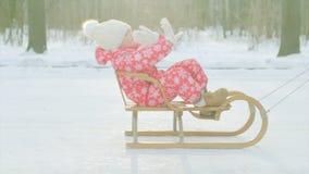 Rapaz pequeno feliz no pequeno trenó no parque do inverno filme