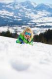 Rapaz pequeno feliz nos óculos de sol que encontram-se na neve e que têm o divertimento Imagem de Stock Royalty Free