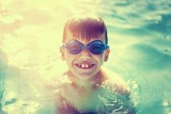 Rapaz pequeno feliz que aprecia férias de verão no vintag da piscina Imagens de Stock Royalty Free
