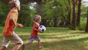 Rapaz pequeno feliz que corre com bola de futebol filme