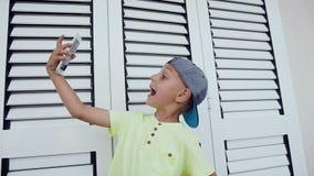 Rapaz pequeno feliz que faz a foto do selfie com o smartphone em casa isolado no fundo branco Adolescente feliz que faz o selfie video estoque