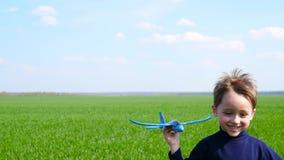 Rapaz pequeno feliz que joga com o avião que corre na grama verde video estoque