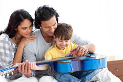 Rapaz pequeno feliz que joga a guitarra com seus pais Foto de Stock