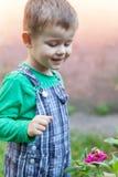 Rapaz pequeno feliz que joga no parque com o caracol no tempo do dia Miúdo observando o caracol Fotos de Stock
