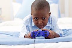 Rapaz pequeno feliz que joga o jogo video Imagens de Stock