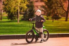 Rapaz pequeno feliz que monta uma bicicleta Fotografia de Stock Royalty Free