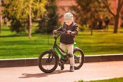 Rapaz pequeno feliz que monta uma bicicleta Fotos de Stock