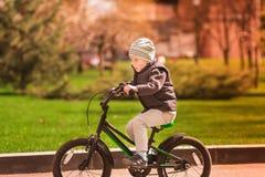 Rapaz pequeno feliz que monta uma bicicleta Fotos de Stock Royalty Free
