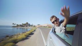Rapaz pequeno feliz que olha da janela de carro, gritaria e acenando durante a viagem por estrada filme