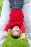 Rapaz pequeno feliz que pendura upside-down no prado fotos de stock royalty free