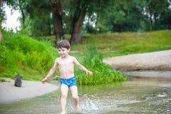 Rapaz pequeno feliz que tem o divertimento e o corredor na água no rio no tempo do dia de verão, estilo de vida exterior, família fotos de stock