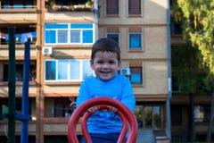 Rapaz pequeno feliz que tem o divertimento na balancê fotos de stock royalty free