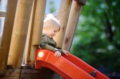 Rapaz pequeno feliz que tem o divertimento na corrediça exterior de playground/on imagens de stock royalty free