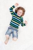 Rapaz pequeno feliz que tem o divertimento no assoalho Fotos de Stock Royalty Free
