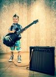 Rapaz pequeno fresco que levanta com guitarra elétrica Fotografia de Stock