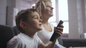 Rapaz pequeno furado que escolhe o programa com telecontrole da tevê video estoque