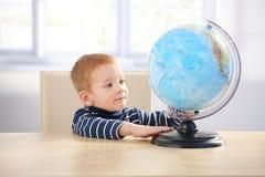 Rapaz pequeno ginger-haired doce que estuda o globo Imagem de Stock Royalty Free