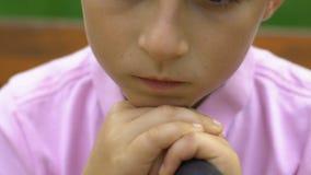 Rapaz pequeno infeliz com o bastão que senta-se no banco no parque, criança triste deficiente filme