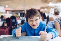 Rapaz pequeno irritado com fome que espera seu jantar imagem de stock royalty free