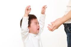 Rapaz pequeno japonês de grito que está sendo mantido por sua mãe Fotografia de Stock Royalty Free