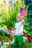 Rapaz pequeno louro de sorriso que guarda a bandeira americana e a ondulação dela Imagens de Stock Royalty Free