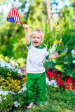 Rapaz pequeno louro descalço que ri e que acena a bandeira americana Fotografia de Stock