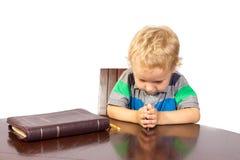 Rapaz pequeno louro que reza ao deus após ter lido a Bíblia imagem de stock