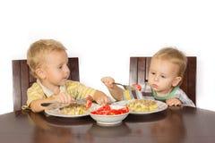 Rapaz pequeno louro que tenta comer com as batatas de uma forquilha com carne e tomates Fotos de Stock