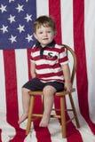 Rapaz pequeno na cadeira com bandeira Imagens de Stock Royalty Free